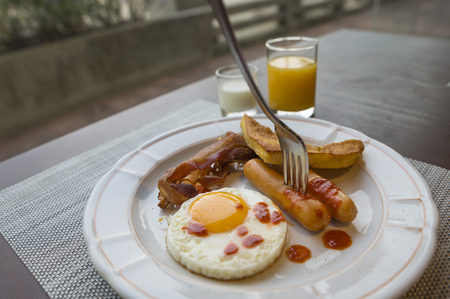 Fork stab on sausage of breakfast meal on wooden table. Breakfast is fried egg, sausages, bacons, potato bread, orange juice and plain yogurt.