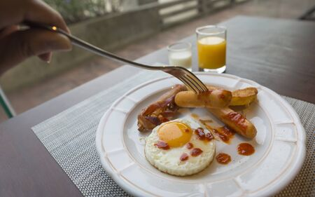 Hand using fork stab on sausage in breakfast meal on wooden table. Breakfast is fried egg, sausages, bacons, potato bread, orange juice and plain yogurt.