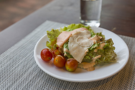 Easy dish of salad with nutural light in the morning.Green salad vegetables, small tomato, ham slice. Selected focus on image. Stock fotó