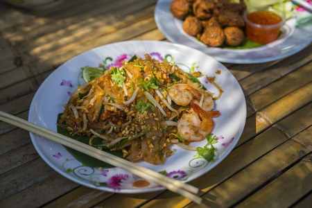 Pad Thai, traditional food of Thailand. Pad Thai with shrimps on banana leaf in white dish. Food dishes on bamboo table. Focus on Pad Thai in front. Backdrop is blurred food. Stock fotó