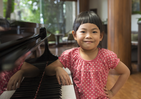 Portrait of Asian little gile with piano in a hotel lobby. Smiling face and look at camera. Wearing pink t-shirt.