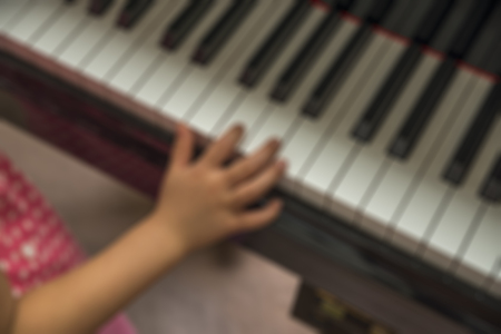 Blurred image little hand on piano. Use fingers on pianos keyboard.