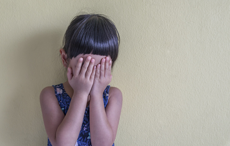 Sad little Asian girl face off by her hand , feel sad and disappointed. Leaning against wall. Space for text