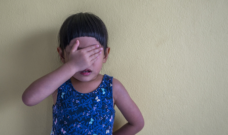Upset Asian little girl. Asian Little girl is crying and stand leaning against wall. Space for text