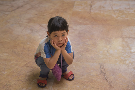 Little Asian girl sitting on floor and making unhappy face, look at camera. Little girls behavior when unsatisfied. 版權商用圖片