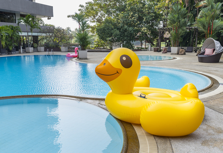 Big inflatable yellow duck at swimming pool without people in a morning. Stock Photo