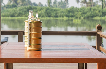 Traditional Thailand or Thais food carrier on wood table in local pavillion at riverside. Blurred backdrop river and tropical forrest. Day light in a morning. Space for text.