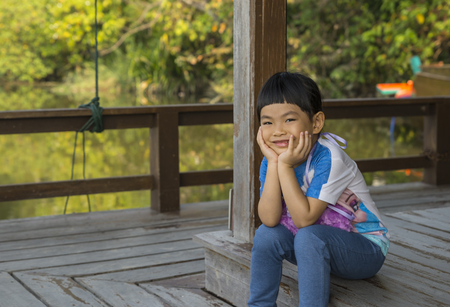 Cute little Asian girl with big smile sitting on the wood floor of the riverside pavilion. Her hands on chin and look at camera. Happy time in holiday with family. Wooden riverside pavilion in Thailand.