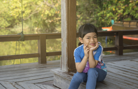 Adorable little Asian girl sitting on the wood floor of the riverside pavilion. Her hands on chin and look at camera.Smiling face of Asian girl with happy time in holiday. Stock fotó