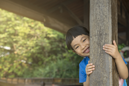 Asian cute little girl feel fun playing hide and seek by sneak behind wooden pole. Little girl with smiling face. Happy in holiday time with family, Space for text.