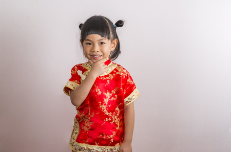 Cute Asian little girl in Chinese dress for Chinese New Year theme. Little girl with smile. Hand touch at chin and look at camera.