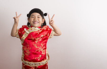 Funny Little girl in Chinese dress. Little girl with big smile showing victory sign with fingers on both hand and look at camera. Stock fotó