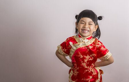 Big smile little girl in Chinese dress for Chinese New Year theme. Little girl in funny action, hands on waist.