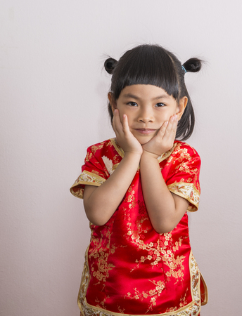 Adorable little girl in red Chinese dress for Chinese New Year theme. Little girl with two hand on cheek and  look at camera.