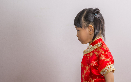 Portrait profile of little girl in Chinese dress for Chinese New Year theme. Four years old little girl in red dress.