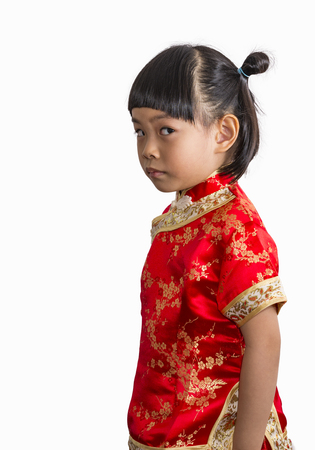 Cute Asian little girl in Chinese dress for Chinese New Year theme. Little girl on white background Stock fotó