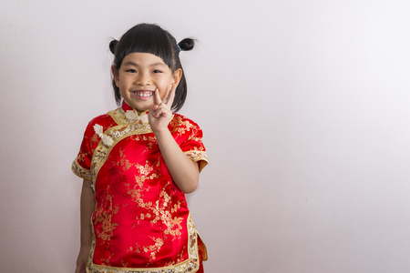 Little girl in Chinese dress. Little girl with big smile and gesture victory by two fingers. Happy face child of Chinese New Year.