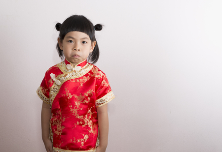Asian little girl in Chinese dress. Little girl in red dress of Chinese culture. Funny face act of little girl by keeping air in mouth, cheek bulge.