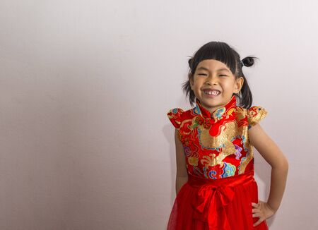 Happy little Asian girl in in modern Chinese tradition costume. Smiling little girl in Chinese New Year theme. Stock fotó