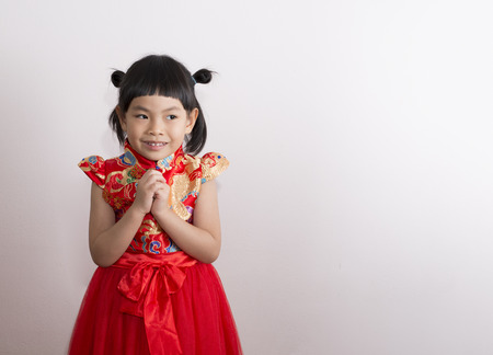 Asian little girl in modern Chinese costume for Chinese New Year. Girl is greeting in Chinese style and looking aside. Space for text.