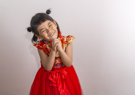 Happy Asian little girl in modern Chinese costume. Girl is greeting in Chinese style and looking camera. Big smile face, Space for text. Stock fotó