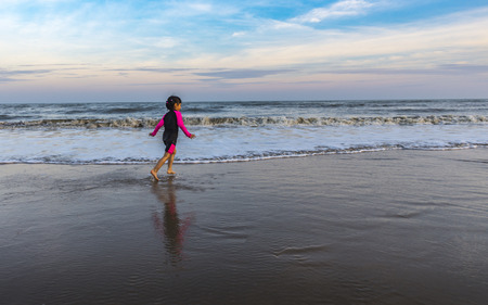 Asian little girl running on the beach. Sky is blue, orange and yellow in sunset time. Space for text.