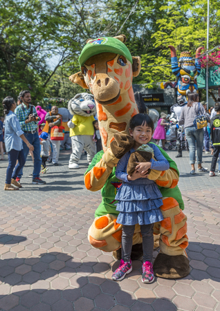 Bangkok, Thailand - Jan 13, 2018 Unidentified little girl is happy with giraffe mascot at Safari World Zoo on holiday. Many tourists in background.