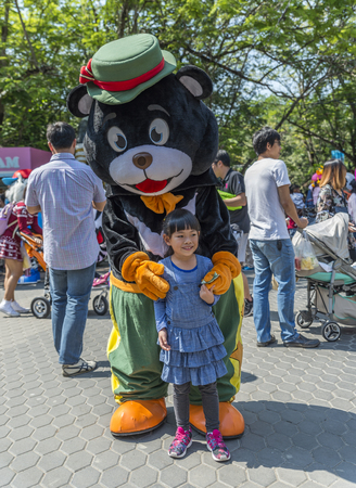 Bangkok, Thailand - Jan 13, 2018 Unidentified little girl is happy with black bear mascot at Safari World Zoo on holiday. Many tourists in background.