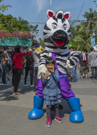 Bangkok, Thailand - Jan 13, 2018 Unidentified little girl is happy with zebra mascot at Safari World Zoo on holiday. Many tourists in background. Sajtókép
