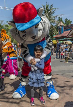 Bangkok, Thailand - Jan 13, 2018 Unidentified little girl is happy with white tiger mascot at Safari World Zoo on holiday. Many tourists in background.
