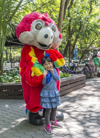 Bangkok, Thailand - Jan 13, 2018 Unidentified little girl is happy with macore mascot at Safari World Zoo on holiday. Many tourists in background.