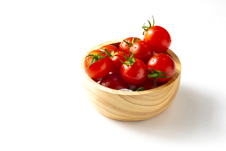 Red tomatoes in small wooden bowl on white background