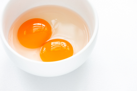 Two raw egg yolks in white bowl