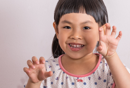 Close up Asian little girl in funny moment, playing and acting as monster or tiger or dragon by showing claws.