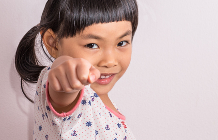 Asian little girl using fist point to camera, big smile, selected focus.