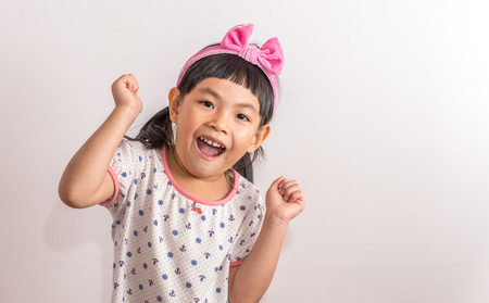 Portrait of child or Asian Thai little girl acting very happy with hands up and big smile.