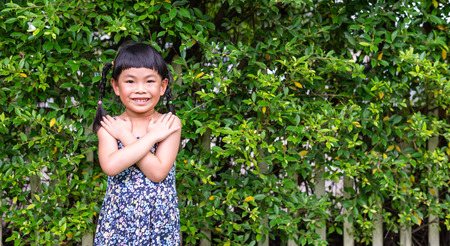 Little girl with big smile standing in front of fence with plant. Cross her arms her on her chest. Concept of love and care. Stock fotó