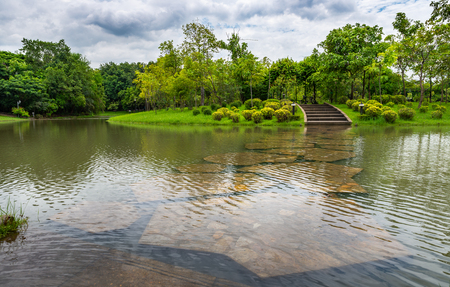 Pathway under water in public park. Small canal in a park. Cloudy sky over a park. Stock fotó