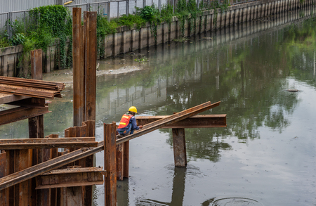 Worker on steel bar at construction site. Working on steel bar over polluted canal. Stock fotó
