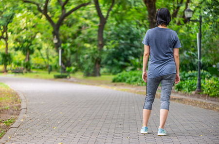 Back side of Woman standing on walk way in a park, sweat on tshirt. Perspective view of walk way in park. Space for text.