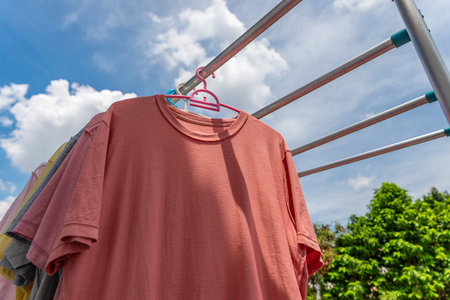 Drying colorful clothes by hanging on bar. Low angle view. Stock fotó