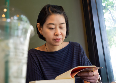 Portrait Asian middle aged woman reading book in cafe or coffee shop. Low angle view.