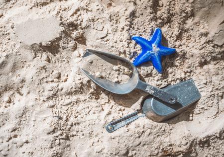 Beach toys on beach sand, a blue starfish and metal shovel