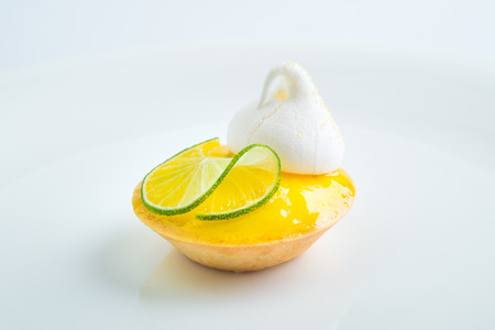 Dilicious lemon tart with decoration on white background.
