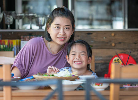 Mother and daughter in a restaurant. Happy time toghter at table food.