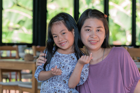 Portrait of mother and little daughter together in a restaurant. Little daughter try to create mini heart with her hands