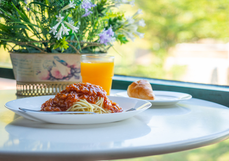Spaghetti bolognese in round shape table in a morning. Image with space for test.