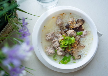 Top view image of rice soup on white table.