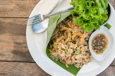 Top view healthy Thai food, Kaw Pad Nam Prick Pra Salid or Stired fried rice with chilli paste, topping with deep fried fish.