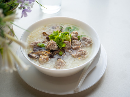 Simple 45 degree angle view Image of rice soup on white table.